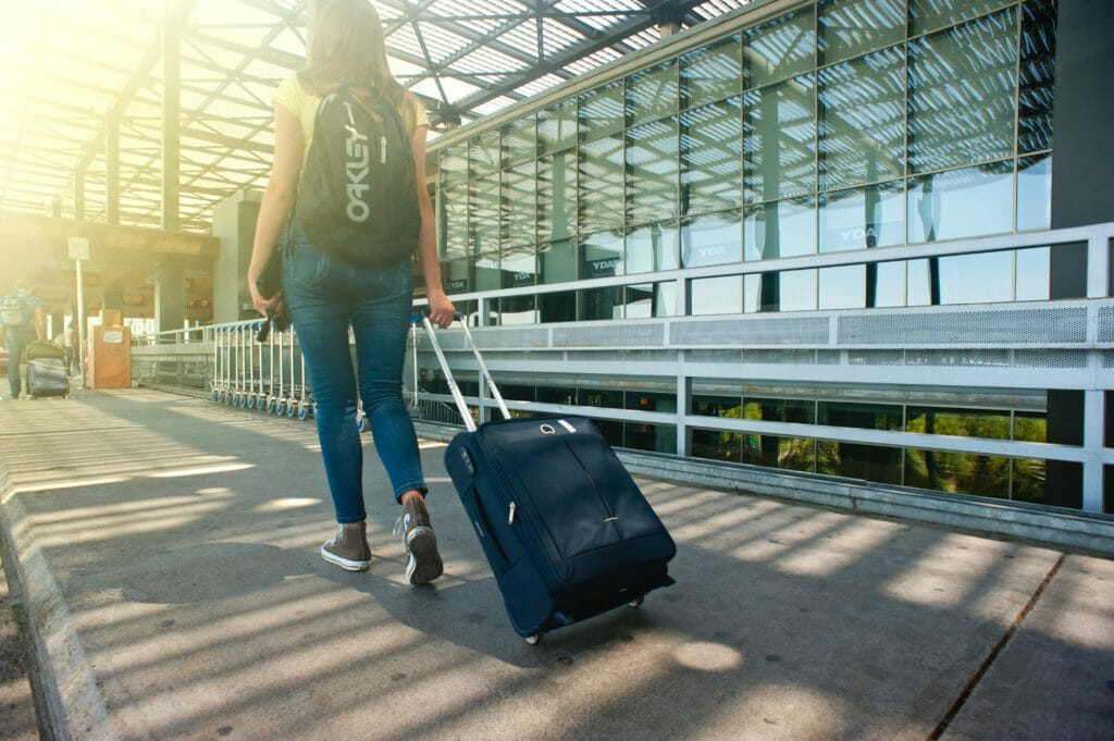 woman walking on pathway while strolling luggage 1008155